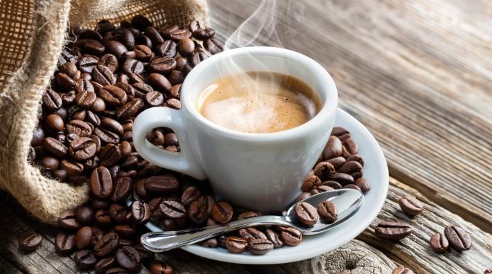 لیوان حاوی قهوه در کیسه پر از دانه های قهوه